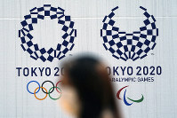 A woman wearing a protective face mask walks near the Tokyo 2020 Olympic and Paralympic Games logo, on April 2, 2020, in Tokyo. (AP Photo/Eugene Hoshiko)