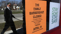 A pedestrian walks by The Family Barbershop, closed due to a Gov. Gretchen Whitmer executive order, in Grosse Pointe Woods, Michigan, on April 2, 2020. (AP Photo/Paul Sancya)