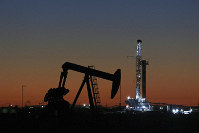 This Oct. 9, 2018 file photo shows an oil rig and pump jack in Midland, Texas. (Jacob Ford/Odessa American via AP)