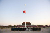 In this photo released by China's Xinhua News Agency, an honor guard stands in formation as a Chinese national flag flies at half-staff at Tiananmen Square in Beijing, on April 4, 2020. (Ju Huanzong/Xinhua via AP)