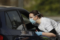 A NHS (National Health Service) worker is tested for Covid-19 at a drive-through testing center in a car park at Chessington World of Adventures, Greater London, on April 4, 2020. (AP Photo/Matt Dunham)