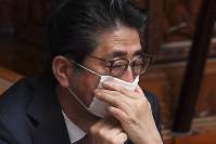 Japanese Prime Minister Shinzo Abe adjusts a face mask during a House of Councillors plenary session on April 3, 2020, in Tokyo. (AP Photo/Eugene Hoshiko)