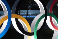 A man jogs past the Olympic rings on March 30, 2020, in Tokyo. (AP Photo/Jae C. Hong)