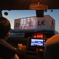 車に乗ったまま映画を見る「ドライブインシアター」を楽しむ親子=山梨県甲斐市で2020年4月5日午後6時34分、大西岳彦撮影