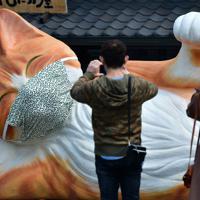 唐草模様のマスクを着けた巨大招き猫=愛知県瀬戸市で2020年4月4日、兵藤公治撮影