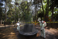 Municipal employees, wearing protective gear, disinfect an area of a public park as a preventive measure against the spread of the new coronavirus, in Mexico City,  April 4, 2020. (AP Photo/Fernando Llano)