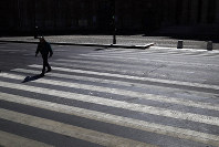 A man crosses an empty street during a nationwide confinement to counter the Covid-19, in Paris,  April 4, 2020. (AP Photo/Christophe Ena)