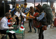 A stranded tourist sanitizes her hand as she registers her name to get a rescue flight back to her country during lockdown in Kathmandu, Nepal, April 4, 2020. (AP Photo/Niranjan Shrestha)