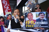 In this Jan. 29, 2019, file photo, protesters demonstrate in support of prominent Chinese human rights lawyer Wang Quanzhang, right on poster, outside the Chinese liaison office in Hong Kong. (AP Photo/Vincent Yu, File)