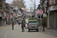 Indian army soldiers stand guard as their colleague shops during a lockdown in Srinagar, Indian controlled Kashmir, March 31, 2020. (AP Photo/ Dar Yasin)