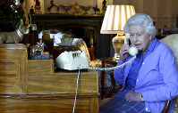 In this photo made available by Buckingham Palace, Britain's Queen Elizabeth II speaks to Prime Minister Boris Johnson from Windsor Castle, Windsor, England, Wednesday March 25, 2020, for her weekly audience. (Buckingham Palace via AP)