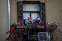 A couple applaud from their balcony in support of the medical staff that are working on the COVID-19 virus outbreak in Barcelona, Spain, Saturday, April 4, 2020. (AP Photo/Emilio Morenatti)