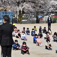 新型コロナウイルス対策のため校庭で行われた始業式で、間隔をあけて座る子供たち=北九州市小倉北区の市立霧丘小で2020年4月6日午前9時25分、森園道子撮影