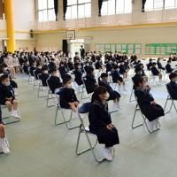 椅子と椅子の間を広げ、離れて座る名山小の新入生ら=鹿児島市で2020年4月6日午前10時25分、白川徹撮影