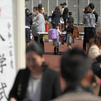 新型コロナウイルスの感染が広がる中、入学式の受付で手をアルコール消毒を行い、マスクをつけ直す新1年生の子供たち=東京都足立区の区立足立小で2020年4月6日午後1時33分、手塚耕一郎撮影
