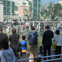 新型コロナウイルスの感染が広がる中、校庭で行われた入学式。中に入れるのは各家族1人なので、外からフェンス越しに大勢の人たちが眺めていた=東京都足立区立足立小で2020年4月6日午後2時15分、手塚耕一郎撮影