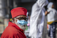 A priest wears a mask to prevent the risk of infection by the new coronavirus, as he attends a Sunday morning mass at the Bole Medhane Alem Ethiopian Orthodox Cathedral in Addis Ababa, Ethiopia, on April 5, 2020. (AP Photo/Mulugeta Ayene)