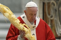 Pope Francis holds a palm branch as he celebrates Palm Sunday Mass behind closed doors in St. Peter's Basilica, at the Vatican, on April 5, 2020, during the lockdown aimed at curbing the spread of the COVID-19 infection, caused by the novel coronavirus. (AP Photo/pool/Alberto Pizzoli)