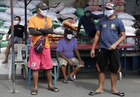 Men wearing protective masks stand near the village hall during an enhanced community quarantine to help curb the spread of the new coronavirus at the usually busy downtown Manila, Philippines, on April 3, 2020. (AP Photo/Aaron Favila)