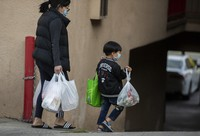 In this April 2, 2020 file photo, an adult and a child, both wearing face masks amid the coronavirus outbreak, carry bags in the Chinatown neighborhood of Los Angeles. (AP Photo/Damian Dovarganes)