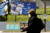 A pedestrian wears a hat and a face mask on Sunset Blvd., in the Echo Park neighborhood of Los Angeles, on April 2, 2020. (AP Photo/Damian Dovarganes)