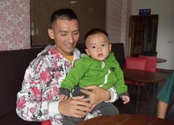 次男の約掌単ちゃんをあやす呉以諾さん=寒渓村で2020年3月14日、福岡静哉撮影