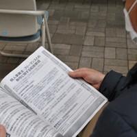 相談窓口で受け取った資料に目を落とす男性=福山市役所で、関東晋慈撮影