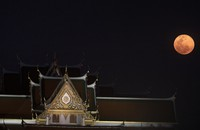 A full moon rises beside the Grand Palace in Bangkok, Thailand, on April 8, 2020. (AP Photo/Sakchai Lalit)