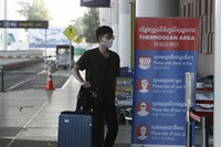 In this April 3, 2020 file photo, a tourist wearing a face mask enters an area of thermo scan at the quiet Phnom Penh International Airport in Phnom Penh, Cambodia. (AP Photo/Heng Sinith)