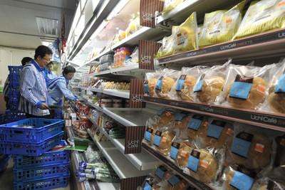 本格的な営業を開始する仮設のコンビニエンスストアで開店準備をする従業員ら。同店は被災した2人のオーナーが経営し、生鮮食品や生活雑貨、デザートなど被災した人たちから要望の強い品物を多くそろえるという=岩手県陸前高田市で2011年4月22日午前5時17分、西本勝撮影