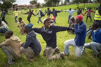 Homeless recyclers and other destitute people, some of whom said they have not eaten in three days, are asked to practice social distancing by police as they lineup in a Johannesburg park, waiting to receive food baskets from private donors, on April 9, 2020. (AP Photo/Jerome Delay)