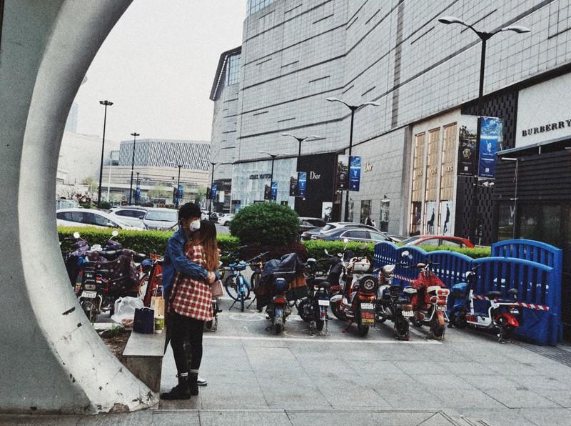 3月下旬から外出規制が段階的に緩和された武漢市の繁華街でマスクをつけたままハグする市民=4月4日撮影、武漢市民提供