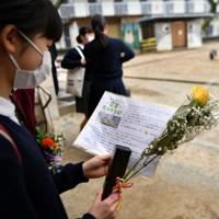 卒業式の後、大和卓也さん・忍さん夫妻から届いた黄色いバラを手にメッセージカードを読む白坪小の児童=熊本市西区で2020年3月19日、清水晃平撮影