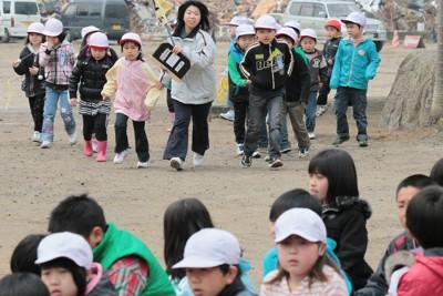 校庭の向こうに被災した街が広がる中、震災後初の避難訓練する児童たち。避難場所まで約1キロの道のりを歩いた=岩手県陸前高田市で2011年4月27日午前10時2分、岩下幸一郎撮影