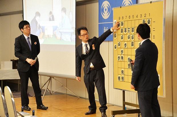 第67回棋王将棋戦第4局の大盤解説会に登場した今泉さん(中央)=2018年2月