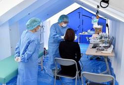 発熱やせきの症状がある人を駐車場の一角に建てられたテント内で診察する医師ら=兵庫県西脇市立西脇病院で2020年4月9日、平川義之撮影
