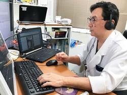テレビ電話越しに患者の体調を尋ねる医師