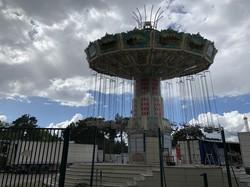 例年初夏にやってくる移動遊園地も営業できず、無人の回転ブランコが。閉まった門の先には、関係者の子供たちの遊ぶ声が響いていた=パリ12区バンセンヌの森で4月18日、筆者撮影