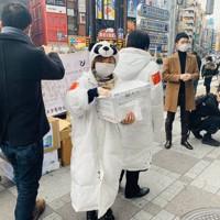 2月29日、JR池袋駅前で中日ボランティア協会も参加した「マスク・パンダ・アクション」活動で、マスクを配るボランティアら=張剣波さん提供