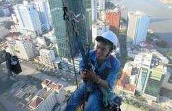 ホーチミンの超高層ビルの展望台から。外壁を清掃する若者と目が合った(写真は筆者撮影)