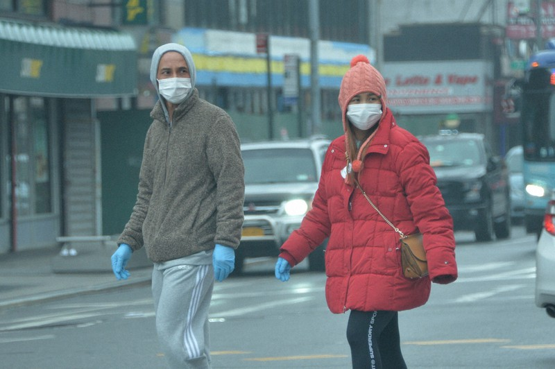 マスクと手袋をして歩く市民=米ニューヨーク市クイーンズ地区で2020年3月29日、隅俊之撮影