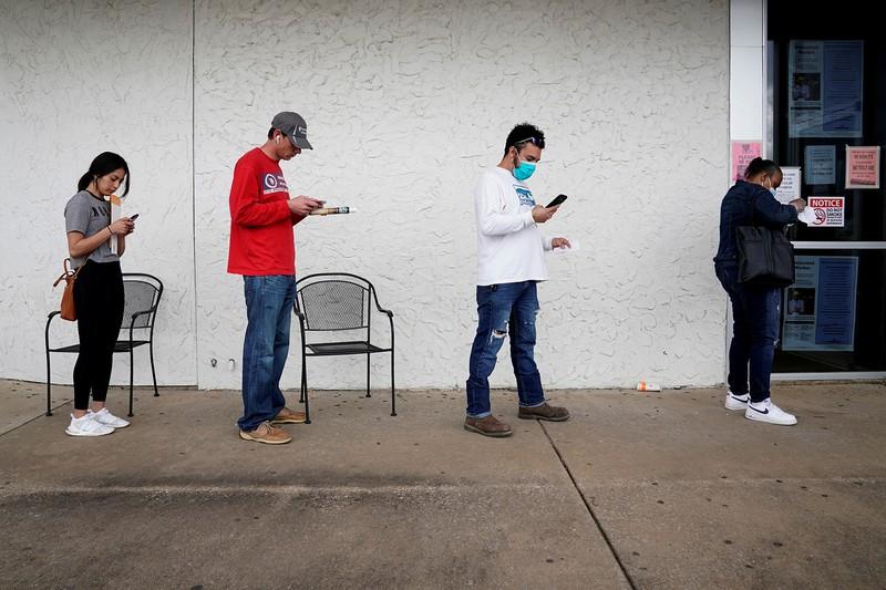 失業保険の申請が急増している(米国アーカンソー州労働力センター前で並ぶ人々)(Reuters)