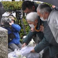 玉栄丸慰霊碑に献花する池渕賢一朗さん(右から2人目)=鳥取県境港市大正町で、柴崎達矢撮影