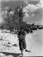 A Japanese woman holding a baby evacuates as U.S. military boats are seen in the background in this photo taken by the U.S. Marines on Saipan in June 1944.  (Photo courtesy of the Okinawa Prefectural Archives)