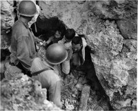 A Japanese man with a child on his back and others come out of a cave to surrender in this photo taken by the U.S. Marines on the island of Tinian in July 1944. (Photo courtesy of the Okinawa Prefectural Archives)