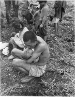 The U.S. military's caption describes the people in the photo as prisoners, and the man in the foreground as feeding candy given to him by a U.S. Marine to his baby after softening it in his mouth. The photo was taken by the U.S. military on the island of Tinian in August 1944. (Photo courtesy of the Okinawa Prefectural Archives)