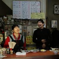 カウンター越しに客と会話を楽しむ店主の畑世志乃さん(左)と長男心太郎さん。夕方の短い時間だけ約10分ほど、周辺ビルに反射した西日がカウンターに差し込む=大阪市福島区で、小出洋平撮影