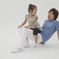 親子体操「タクシー」 親は子どもをおなかにのせ、腰を浮かせて運ぶ。お風呂に入る時など日常生活の合間に行える。子どもはバランス感覚を養い、親は二の腕の筋肉を引き締めることができる=「親子でからだあそび」より