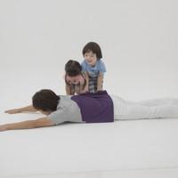 親子体操「たたみ返し」 うつぶせに寝ている親をひっくり返すことができたら、子どもの勝ち。親子で全身の筋肉を鍛えられる=「親子でからだあそび」より