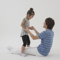 親子体操「グーパージャンプ」 親が伸ばした脚を開いて閉じてと繰り返し、子どもはタイミングを合わせてジャンプする。最初は親子で手をつなぎながらジャンプすると安全。最初はゆっくりとしたテンポで徐々にスピードアップ。子どもはリズム感を養って縄跳びが上手になるかも。親にとっては脚の引き締め効果を期待できる=「親子でからだあそび」より